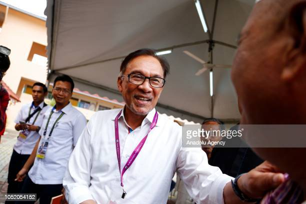 Anwar Ibrahim leader of the Pakatan Harapan coalition shakes hands with voters at a polling station for byelection in Port Dickson on October 13 2018...