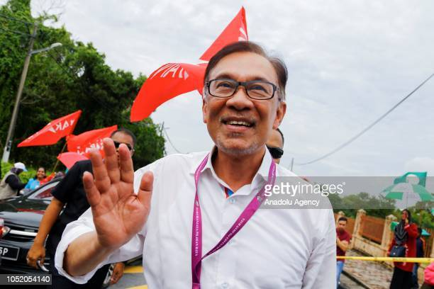 Anwar Ibrahim leader of the Pakatan Harapan Coalition waves to his supporters as he arrives at a polling station on October 13 2018 in Port Dickson...