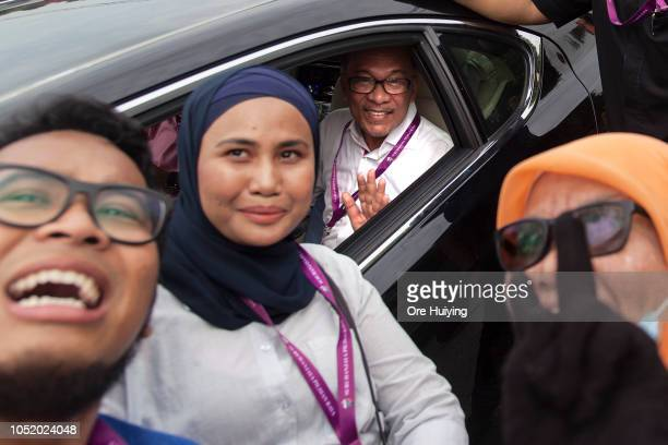 Anwar Ibrahim poses for a photo with his supporters as he departs a polling station on October 13 2018 in Port Dickson Malaysia Malaysia's prime...