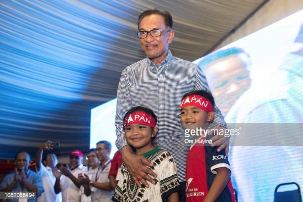 Anwar Ibrahim poses for a photo with his supporters outside the party's headquarters after he wins the byelection on October 13 2018 in Port Dickson...