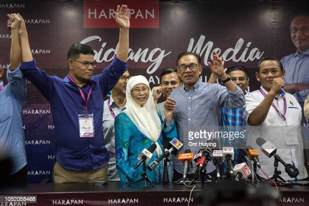 Anwar Ibrahim poses for a photo with members of the Pakatan Harapan during a press conference at the party's headquarters after he wins the...