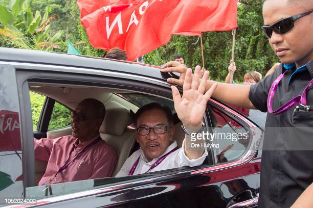 Anwar Ibrahim waves at his supporters as he arrives at a polling station on October 13 2018 in Port Dickson Malaysia Malaysia's prime...