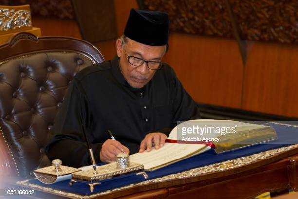 Anwar Ibrahim writes on a book after taking his oath as a Member of Parliament during the swearingin ceremony at the Parliament House in Kuala Lumpur...