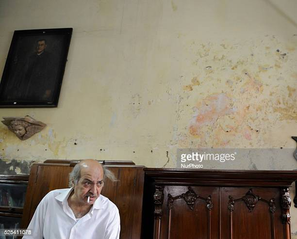Anwar Saleem the elder brother with a cigarette in front of an old painting and an old piece of furniture during the old clothes auction at The...