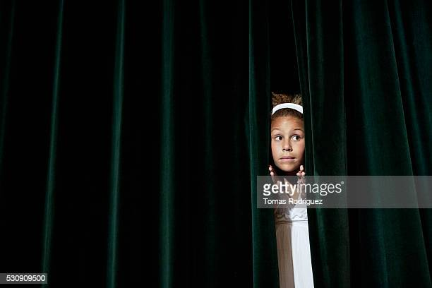 Anxious actress looking through stage curtain