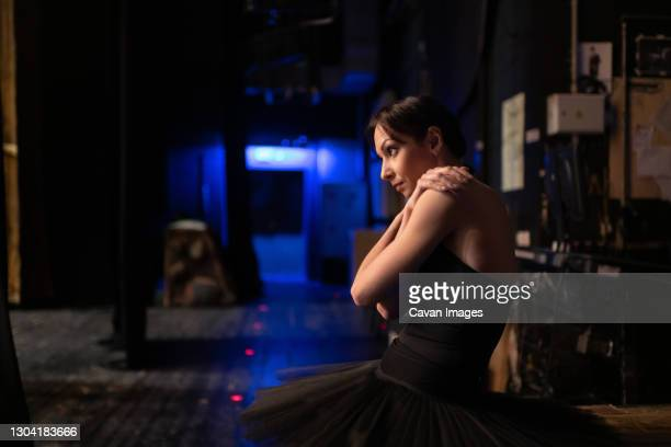 anxious ballet dancer stretching shoulders - rehearsal stock pictures, royalty-free photos & images