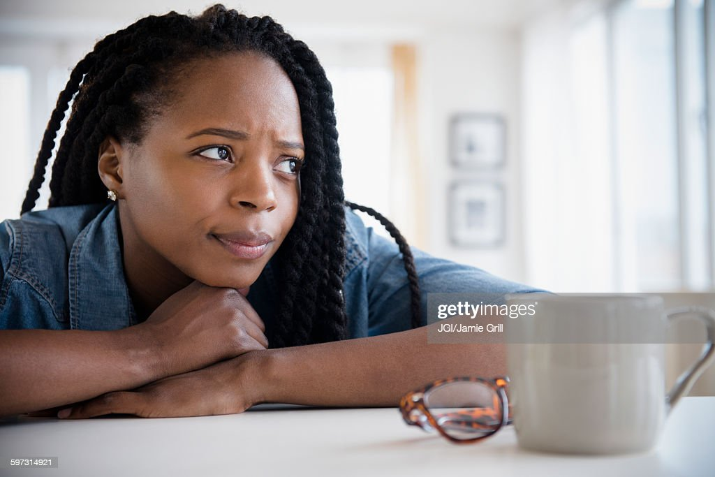 Anxious Black woman resting chin on hands : Stock Photo