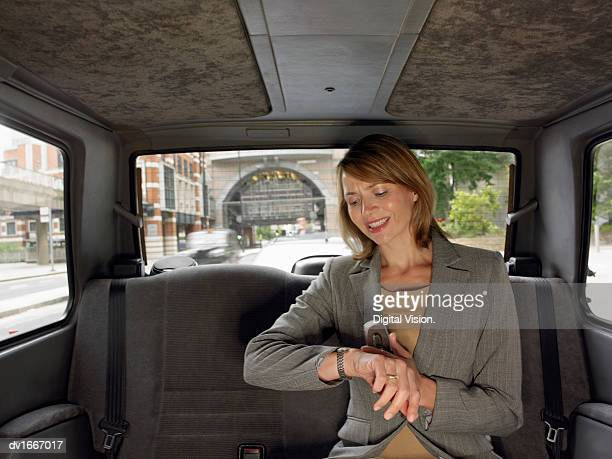 Anxious Businesswoman Travelling in the Back Seat of a Taxi Checking the Time on Her Watch