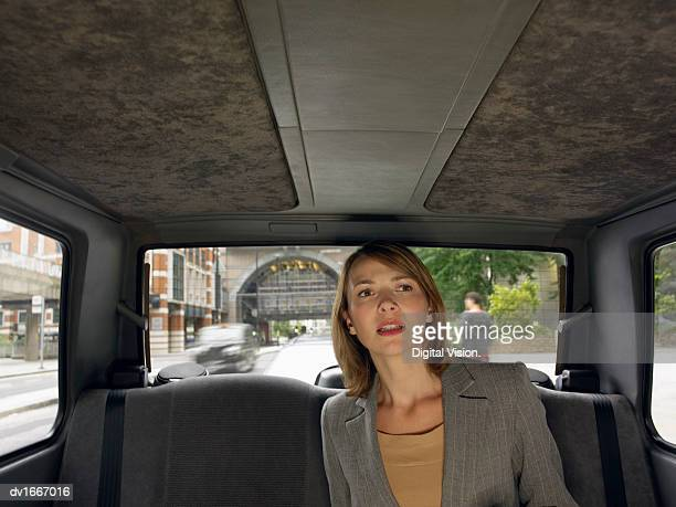 Anxious Businesswoman Travelling in the Back Seat of a Taxi
