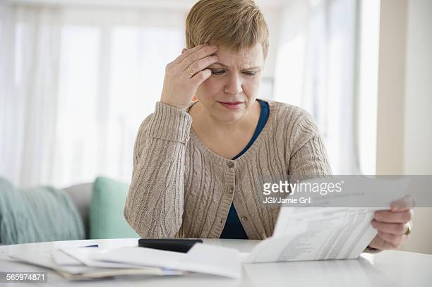 Anxious Caucasian woman paying bills