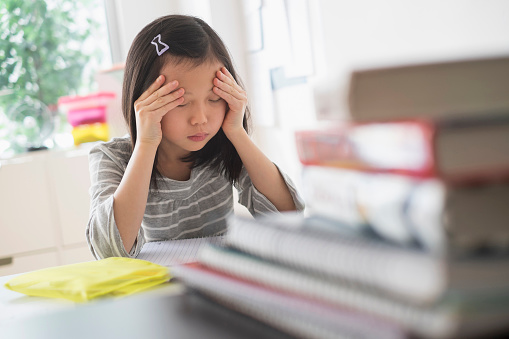 Anxious Chinese student rubbing forehead doing homework - gettyimageskorea
