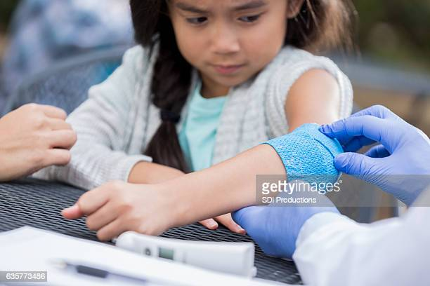 anxious little girl gets bandage at outdoor free clinic - bandage stock photos and pictures