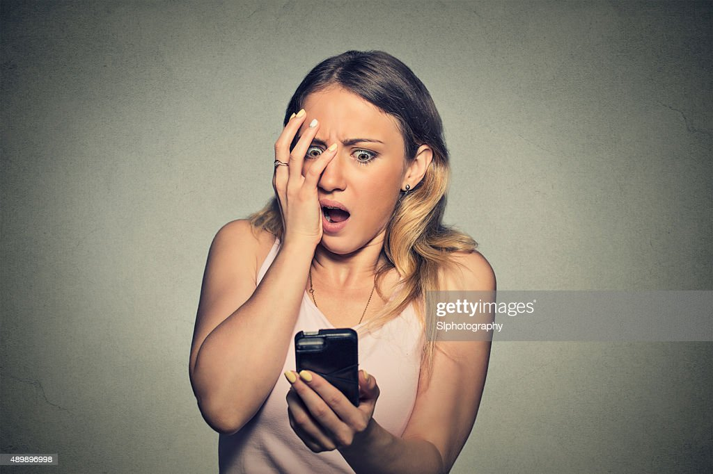 anxious scared girl looking at phone seeing bad news : Stock Photo
