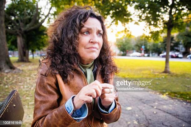 anxieuse senior femme en crise à l'extérieur dans le parc un après-midi de plein air - femme battue photos et images de collection