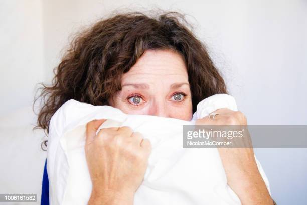 anxious senior woman in crisis screaming in pillow - menopause stock pictures, royalty-free photos & images