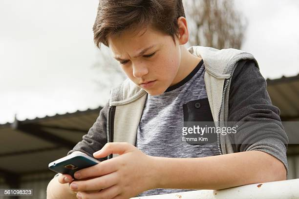 Anxious teenage boy reading smartphone text message