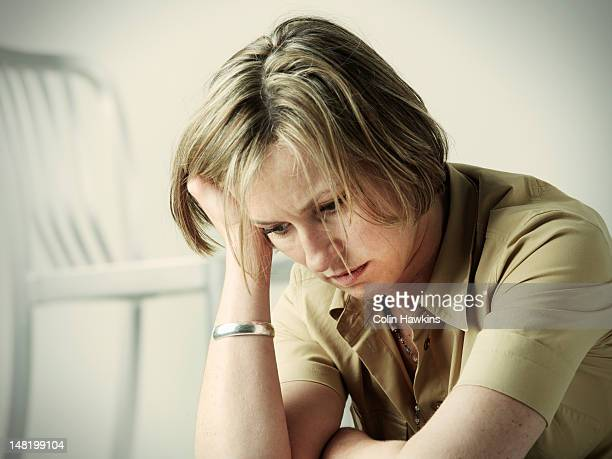 anxious woman resting head in hand - head in hands stock pictures, royalty-free photos & images