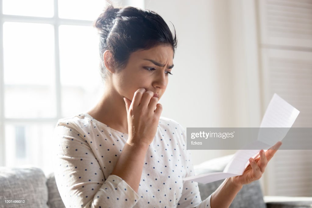 Anxious young woman get unpleasant news in letter : Stock Photo