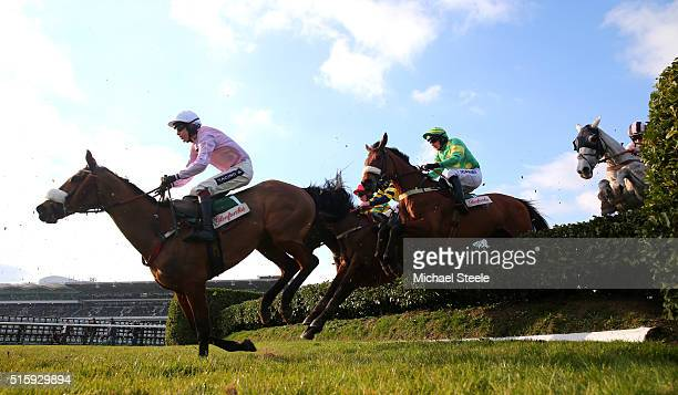 Any Currency ridden by Aidan Coleman leads over a flight in the Glenfarclas Chase on Ladies Day of the Cheltenham Festival at Cheltenham Racecourse...