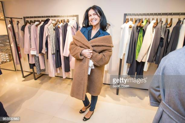 Anya Uritsky tries on a coat at Max Mara's Newbury St location as it celebrates Boston ICA's Watershed Gala on May 1 2018 in Boston Massachusetts