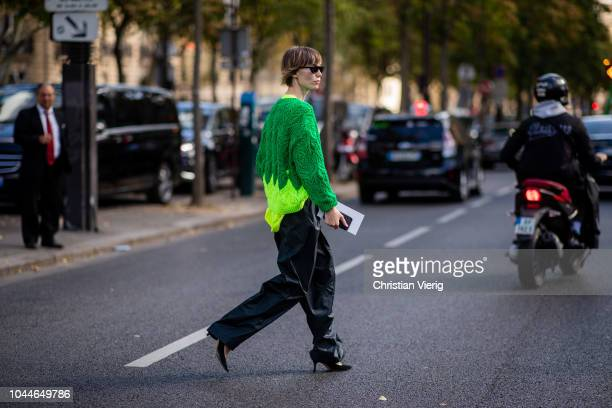 Anya Ziourova wearing green knit black pants is seen outside Sacai during Paris Fashion Week Womenswear Spring/Summer 2019 on October 1 2018 in Paris...