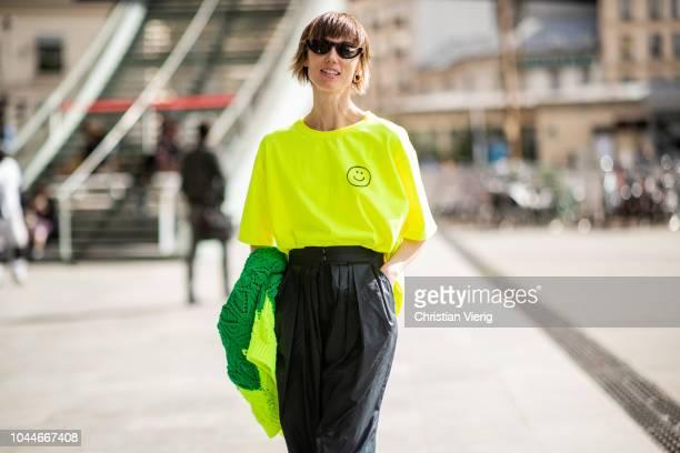 Anya Ziourova wearing neon tshirt black wide leg pants is seen outside Giambattista Valli during Paris Fashion Week Womenswear Spring/Summer 2019 on...