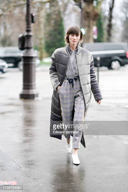 Anya Ziourova wears a gray puffer long coat checked gray outfit white shoes outside Alexandre Vauthier during Paris Fashion Week Haute Couture Spring...