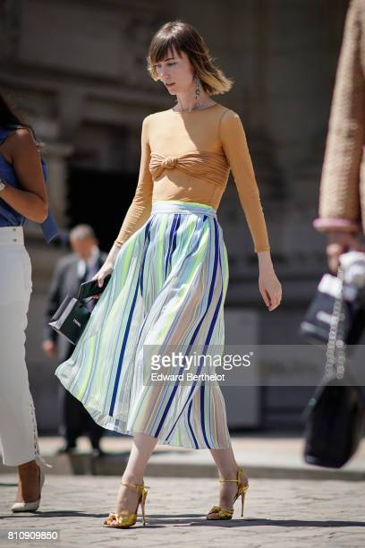 Anya Ziourova wears an orange top a multicolor striped skirt yellow heels shoes outside the Chanel show during Paris Fashion Week Haute Couture...