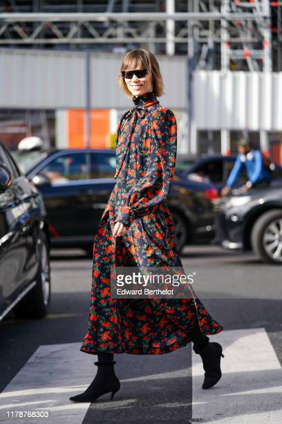 Anya Ziourova wears sunglasses, a hi-neck, long sleeves, red floral print, black long and flowing pleated dress with a bow at the collar, black...