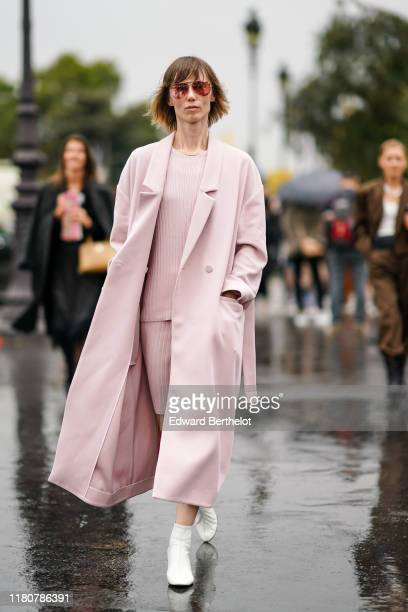 Anya Ziourova wears sunglasses a pink long coat a pink top a pink skirt white shoes outside Chanel during Paris Fashion Week Womenswear Spring Summer...
