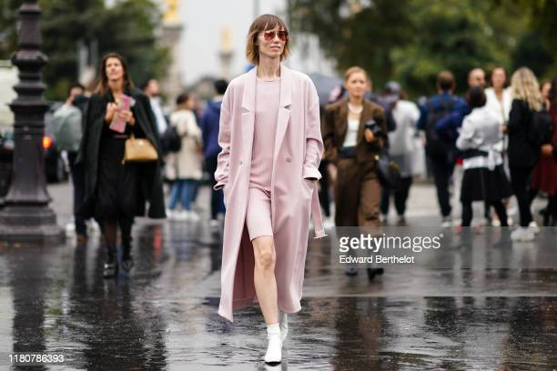 Anya Ziourova wears sunglasses, a pink long coat, a pink top, a pink skirt, white shoes, outside Chanel, during Paris Fashion Week - Womenswear...