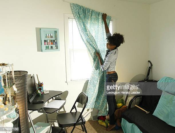 Anyssa Roberts hangs Xhilaration Feather Chevron Light Blocking Window Panels in Turquoise from Target $2999 as she shows some interior design...