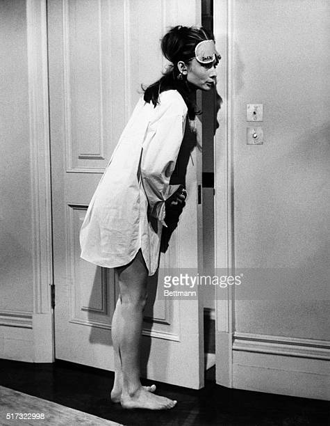 1/14/61 Anything but prosaic in terms of costume screen star Audrey Hepburn listens mischievously at the door in a scene from her latest movie...