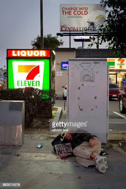 Homeless man with cardboard sign sleeping on the sidewalk in front of a 7Eleven in Pacific Beach California