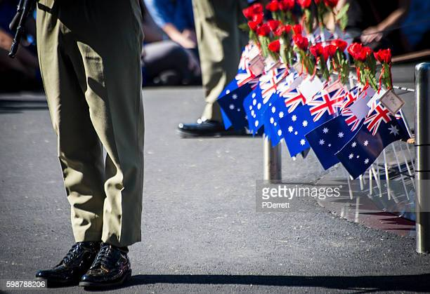 Anzac Day.Soldiers legs and Australian flags and poppies.
