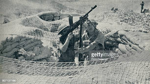 Anzacs on Guard in Egypt' . Soldiers from New Zealand stationed in Egypt practicing the Bren gun technique. From The War in Pictures. [Odhams Press...