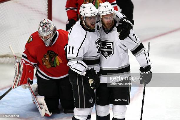 Anze Kopitar and Jeff Carter of the Los Angeles Kings celebrate after Kopitar scored a goal in the third period against goalie Corey Crawford of the...
