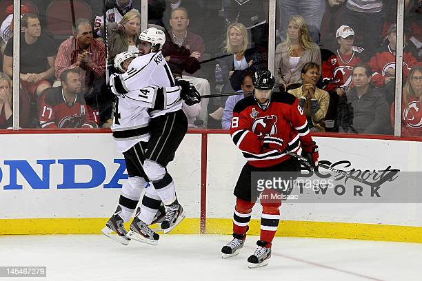 Anze Kopitar of the Los Angeles Kings celebrates with Justin Williams after scoring the game winning goal against the New Jersey Devils as Dainius...