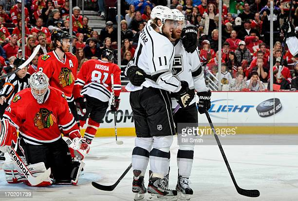 Anze Kopitar of the Los Angeles Kings celebrates with teammate Jeff Carter after scoring in the third period to tie the game as goalie Corey Crawford...