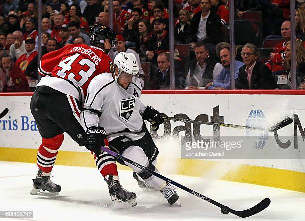 Anze Kopitar of the Los Angeles Kings controls he puck under pressure from Viktor Svedberg of the Chicago Blackhawks at the United Center on November...