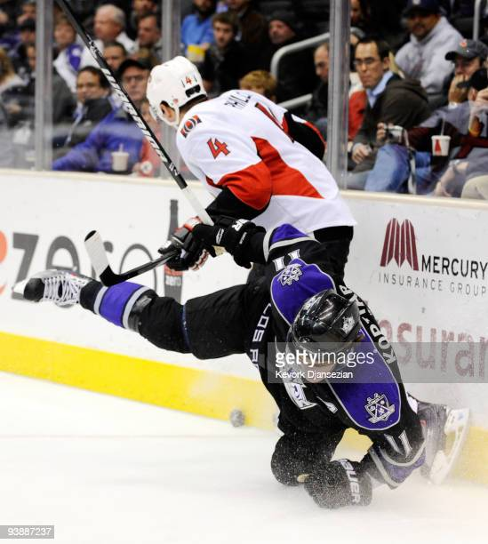 Anze Kopitar of the Los Angeles Kings crashes against the boards as Chris Phillips of the Ottawa Senators defends during third period of the NHL...