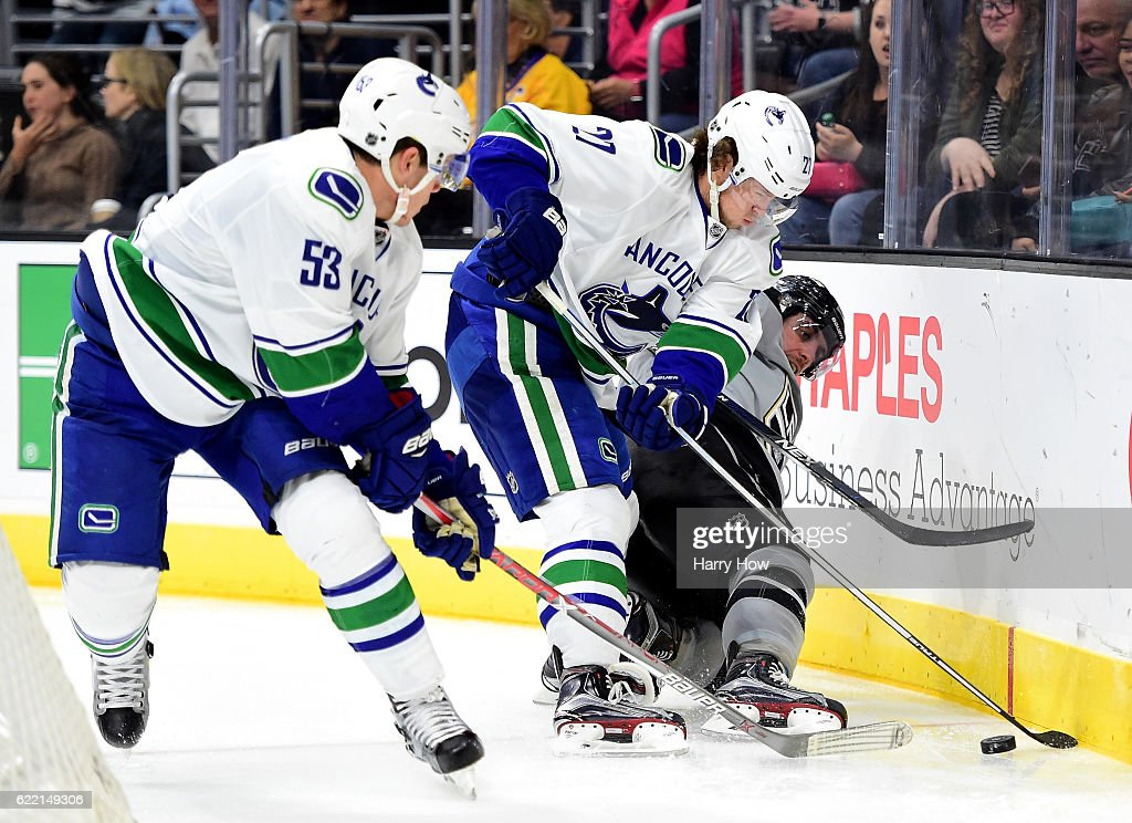 Anze Kopitar #11 of the Los Angeles Kings falls to the ice as Ben Hutton #27 and Bo Horvat #53 of the Vancouver Canucks take the puck at Staples Center on October 22, 2016 in Los Angeles, California.
