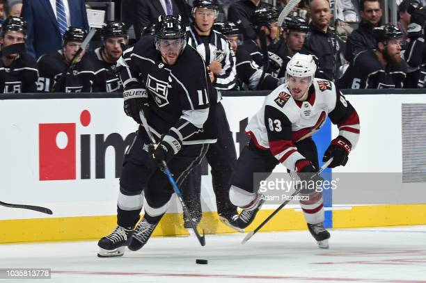 Anze Kopitar of the Los Angeles Kings handles the puck against Conor Garland of the Arizona Coyotes during a preseason game at STAPLES Center on...