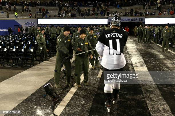 Anze Kopitar of the Los Angeles Kings hands his stick to an Air Force Cadet on his way back to the locker room after the 2020 NHL Stadium Series game...