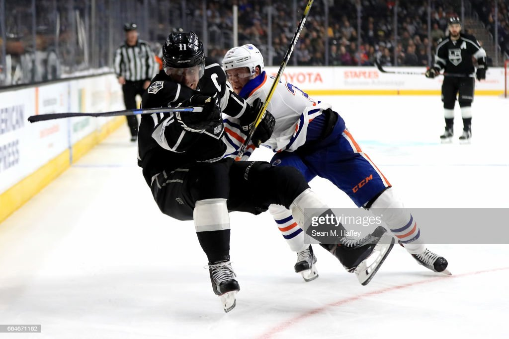 Anze Kopitar #11 of the Los Angeles Kings is checked by Drake Caggiula #36 of the Edmonton Oilers during the second period of a game at Staples Center on April 4, 2017 in Los Angeles, California.