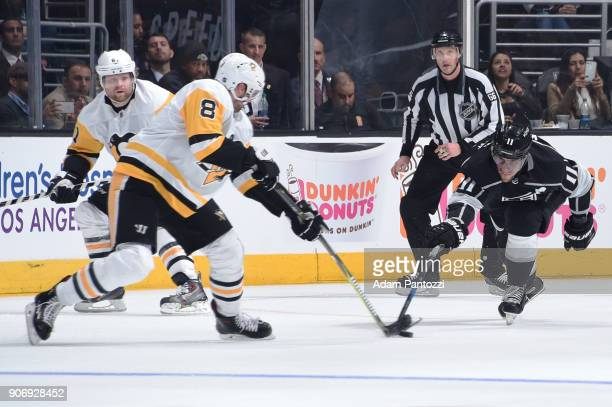 Anze Kopitar of the Los Angeles Kings reaches for the puck against Brian Dumoulin of the Pittsburgh Penguins at STAPLES Center on January 18 2018 in...