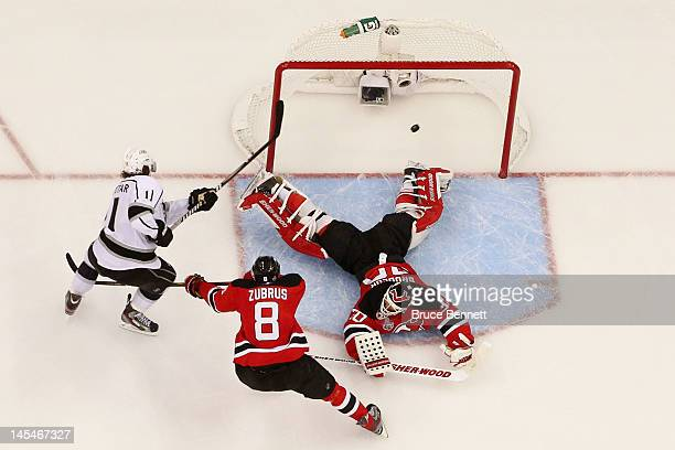 Anze Kopitar of the Los Angeles Kings shoots the game winning goal in overtime against Dainius Zubrus and Martin Brodeur of the New Jersey Devils...