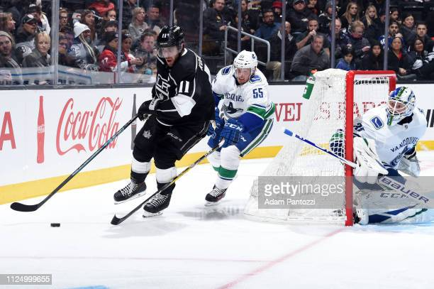 Anze Kopitar of the Los Angeles Kings skates with the puck while pursued by Alex Biega of the Vancouver Canucks as Goaltender Jacob Markstrom of the...