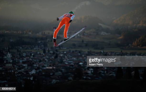 Anze Semenic of Slovenia soars through the air during his training jump on Day 1 of the 65th Four Hills Tournament ski jumping event on December 29...