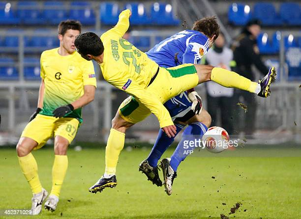Anzhi Makhachkala's midfielder Ilya Maksimov and Nigerian defender Dele Adeleye vie with FC Sheriff Tiraspol's goalkeeper Vjekoslav Tomic during...